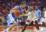 North Carolina's Luke Maye, left, dribbles down the baseline while defended by Clemson's Elijah Thomas during the first half of an NCAA college basketball game Saturday, March 2, 2019, in Clemson, S.C. (AP Photo/Richard Shiro)