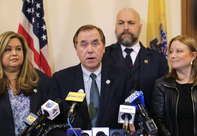 FILE- In this March 25, 2019, file photo, Assembly Speaker Craig Coughlin, center, speaks to reporters in Trenton, N.J. A New Jersey Assembly voting session that had been scheduled for Monday, Nov. 23, 2020, that was to include a measure setting up the new recreational marijuana market has been canceled, Coughlin said Friday, Nov. 20. (AP Photo/Seth Wenig, File)