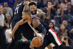Portland Trail Blazers guard Damian Lillard, foreground, dribbles against Golden State Warriors guard Ky Bowman during the first half of an NBA basketball game in San Francisco, Monday, Nov. 4, 2019. (AP Photo/Jeff Chiu)