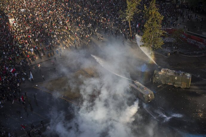 Demonstrators are sprayed by a police water cannon during an anti-government protest in Santiago, Chile, Friday, Nov. 1, 2019. Chile has been facing days of unrest, triggered by a relatively minor increase in subway fares. The protests have shaken a nation noted for economic stability over the past decades, which has seen steadily declining poverty despite persistent high rates of inequality. (AP Photo/Rodrigo Abd)