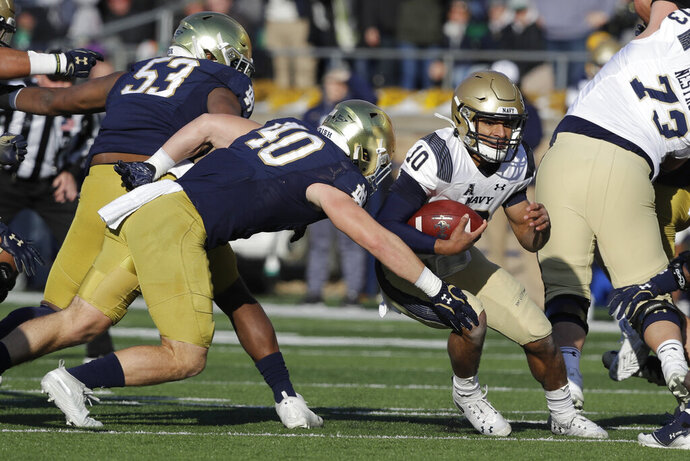 Navy quarterback Malcolm Perry (10) is tackled by Notre Dame linebacker Drew White (40) during the first half of an NCAA college football game, Saturday, Nov. 16, 2019, in South Bend, Ind. (AP Photo/Darron Cummings)