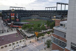 In a photo taken Saturday, June 27, 2020, an elevated deck at a Hilton hotel, right, is seen adjacent to the Oriole Park at Camden Yards stadium along West Camden Street in Baltimore. With the baseball season starting amidst coronavirus restrictions limiting fans from attending games, tall structures such as the Hilton hotel will offer a bird's eye view of games. (AP Photo/Julio Cortez)