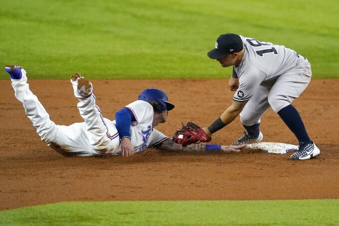 Texas Rangers' Jonah Heim, left, gets back to second safely ahead of the attempted tag by New York Yankees second baseman Rougned Odor, right, in the third inning of a baseball game in Arlington, Texas, Tuesday, May 18, 2021.  (AP Photo/Tony Gutierrez)