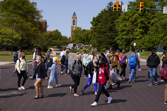 FILE - In this Sept. 10, 2020, file photo, masked students cross an intersection on the campus of Ball State University in Muncie, Ind. President Donald Trump's startling COVID-19 diagnosis serves as a cruel reminder of the pervasive spread of the coronavirus in the United States and shows how tenuous of a grip the nation has on the crisis, health experts said. (AP Photo/Michael Conroy, File)