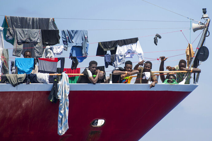 Migrants dry their clothes aboard a tourist boats some 20 kilometers from Malta, Tuesday, June 2, 2020. More than 400 migrants are living aboard pleasure cruise vessels, bobbing in the sea off Malta, many of them for weeks now. Rescued from human traffickers' unseaworthy boats in several operations in the central Mediterranean since late April, the migrants, along with the Maltese government, are waiting for European Union countries to offer to take them. (AP Photo/Rene' Rossignaud)