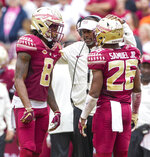 Florida State head coach Willie Taggart talks with defensive backs Stanford Samuels III (8) and Asante Samuel Jr. (26) in the second half of an NCAA college football game against Florida in Tallahassee, Fla., Saturday, Nov. 24, 2018. Florida defeated Florida State 41-14. (AP Photo/Mark Wallheiser)