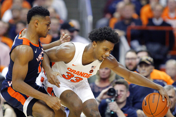 Syracuse's Elijah Hughes, right, controls the ball under pressure from Virginia's Casey Morsell, left, during the first half of an NCAA college basketball game in Syracuse, N.Y., Wednesday, Nov. 6, 2019. (AP Photo/Nick Lisi)