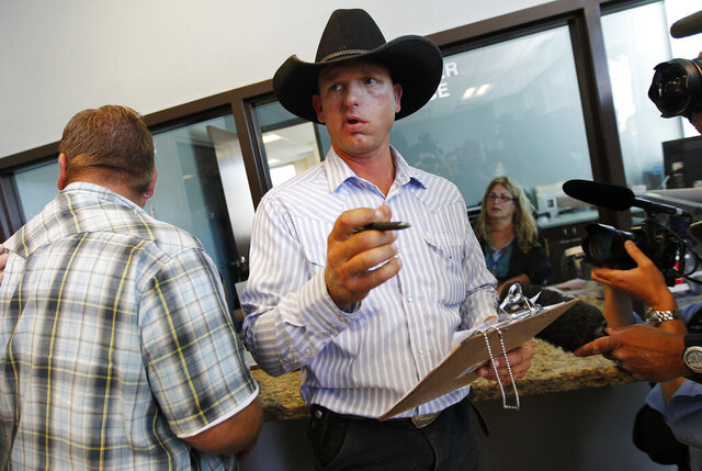 FILE - In this May 2, 2014, file photo, Ryan Bundy, son of rancher Cliven Bundy, gets the paperwork to file official complaints and press charges against federal law enforcement agents at Las Vegas Metro Police headquarters in Las Vegas. Attorney Alyssa Bell, representing co-defendant Ryan Bundy, said Wednesday, Jan. 15, 2020, that prosecutors' misdeeds forced defendants' attorneys to ask the judge to dismiss the case midway through proceedings. (Jason Bean/Las Vegas Review-Journal via AP, File)