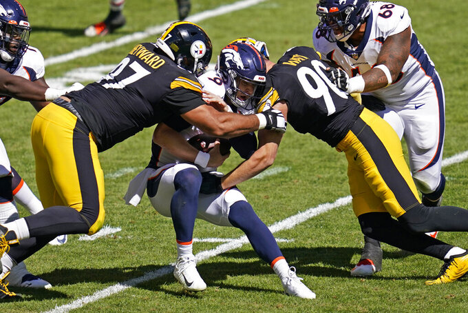 FILE - In this Sept. 20, 2020, file photo, Denver Broncos quarterback Jeff Driskel (9) is sacked by Pittsburgh Steelers defensive tackle Cameron Heyward (97) and T.J. Watt (90) during the first half of an NFL football game in Pittsburgh. In the midst of an NFL season that is course to set records for the most points and touchdowns, the Baltimore Ravens and Pittsburgh Steelers are winning on the strength of their defense. (AP Photo/Keith Srakocic, File)