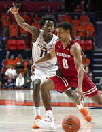 Wisconsin guard D'Mitrik Trice (0) moves the ball against Illinois guard Ayo Dosunmu (11) during the second half of an NCAA college basketball game in Champaign, Ill., Wednesday, Jan. 23, 2019. (AP Photo/Stephen Haas)