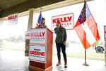 Republican congressional candidate Marjorie Taylor Greene, right, speaks as Sen. Kelly Loeffler, R-Ga., listens during a news conference on Thursday, Oct. 15, 2020, in Dallas, Ga. (AP Photo/Brynn Anderson)