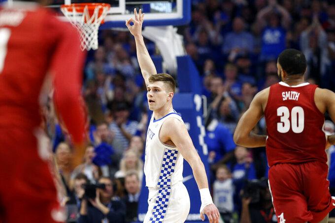 Kentucky's Nate Sestina, center, celebrates a made 3-point shot near Alabama's Galin Smith (30) during the first half of an NCAA college basketball game in Lexington, Ky., Saturday, Jan 11, 2020. (AP Photo/James Crisp)