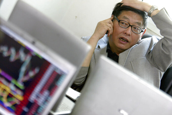 """In this May 11, 2006, photo, Chinese investor Yang Huaiding speaks on the phone while looking at a computer terminal in Shanghai, China. News reports say Yang, former factory worker known as """"China's First Shareholder"""" after he amassed a fortune trading in the country's infant financial markets starting in the 1980s has died Sunday, June 13, 2021. (Chinatopix via AP)"""