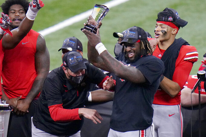 Ohio State running back Trey Sermon, right, is congratulated by head coach Ryan Day, left, while holding most valuable player trophy following the Big Ten championship NCAA college football game, Saturday, Dec. 19, 2020, in Indianapolis. Ohio State defeated Northwestern 22-10. (AP Photo/AJ Mast)