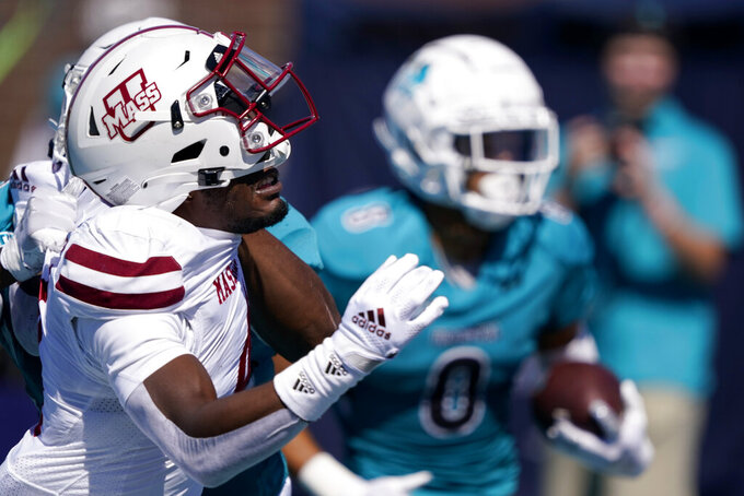 Massachusetts defensive back Noah Boykin is blocked by Coastal Carolina tight end Isaiah Likely as wide receiver Tyson Mobley runs for a touchdown during the first half of an NCAA college football game on Saturday, Sept. 25, 2021, in Conway, S.C. (AP Photo/Chris Carlson)