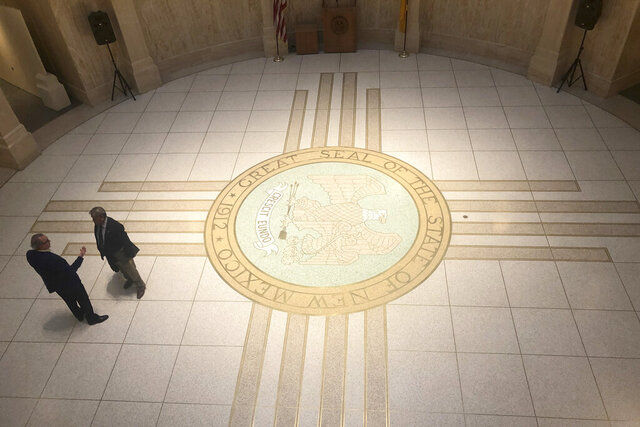 New Mexico statehouse staff talk during a break on Wednesday, Feb. 19, 2020, at the New Mexico Rotunda in Santa Fe, N.M. State lawmakers are racing through the final days of a 30-day Legislative session, which ends Thursday. (AP Photo/Russell Contreras)
