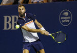 Benoit Paire, of France, hits a return to Steve Johnson, of the United States, during the Winston-Salem Open tennis tournament in Winston-Salem, N.C., Friday, Aug. 23, 2019. (AP Photo/Nell Redmond)