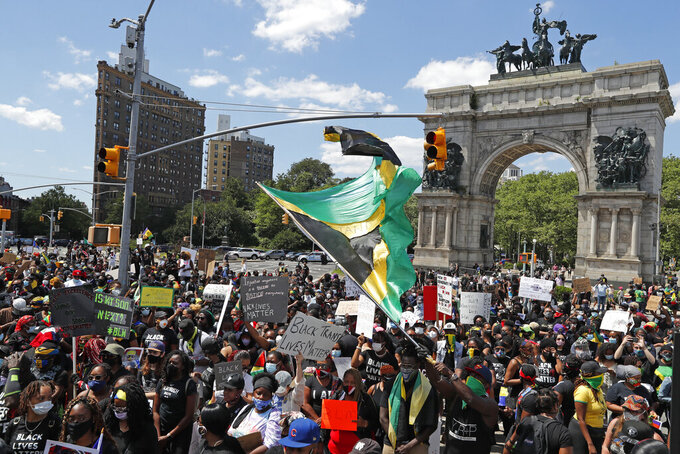 People gather to listen to speakers, rap artists and music during a Caribbean-led Black Lives Matter rally at Brooklyn's Grand Army Plaza, Sunday, June 14, 2020, in New York. Protests have continued since the May 25th death of George Floyd, a black man who died in police custody in Minneapolis. (AP Photo/Kathy Willens)