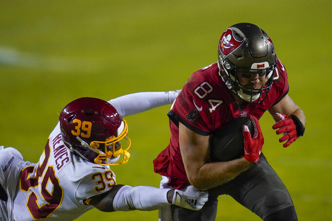 Tampa Bay Buccaneers tight end Cameron Brate (84) breaks away from Washington Football Team free safety Jeremy Reaves (39) as he runs with the ball during the first half of an NFL wild-card playoff football game, Saturday, Jan. 9, 2021, in Landover, Md. (AP Photo/Julio Cortez)