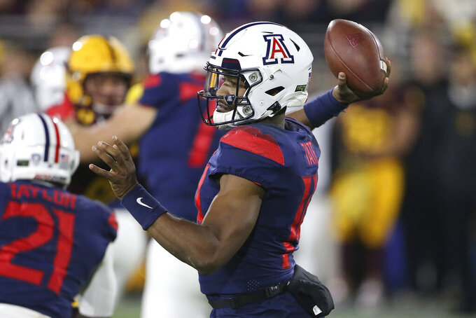 Arizona's Khalil Tate (14) looks to pass against Arizona State's defense during the first half of an NCAA college football game, Saturday, Nov. 30, 2019, in Tempe, Ariz. (AP Photo/Darryl Webb)
