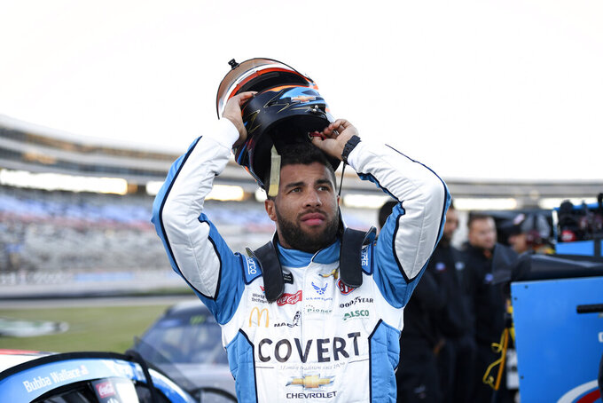 FILE - In this Saturday, Nov. 2, 2019, file photo, Bubba Wallace prepares by his car for qualifying for a NASCAR Cup Series auto race at Texas Motor Speedway in Fort Worth, Texas. On Saturday, Nov. 9, 2019, Wallace was fined $50,000 by NASCAR for causing a caution the week before at Texas that affected the race for at least one playoff driver. (AP Photo/Larry Papke, File)