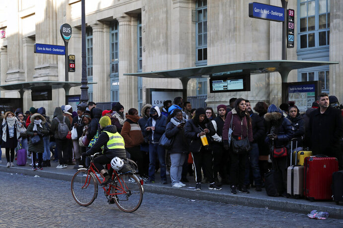 A woman rides her bicycle as commuters wait for a bus at Gare du Nord Station, in Paris, Tuesday, Dec. 10, 2019. Only about a fifth of French trains ran normally Tuesday, frustrating tourists finding empty train stations, and most Paris subways were at a halt. French airport workers, teachers and others joined nationwide strikes Tuesday as unions cranked up pressure on the government to scrap changes to the national retirement system. (AP Photo/Francois Mori)