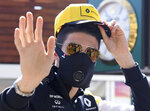 FILE - In this March 12, 2020, file photo Renault driver Esteban Ocon of France waves as he arrives wearing a mask to the Australian Formula One Grand Prix in Melbourne. The 2021 Australian Grand Prix has been canceled after local organizers and Formula One couldn't come up with a compromise over Australia's strict travel and quarantine issues relating to the COVID-19 pandemic. (AP Photo/Andy Brownbill, File)