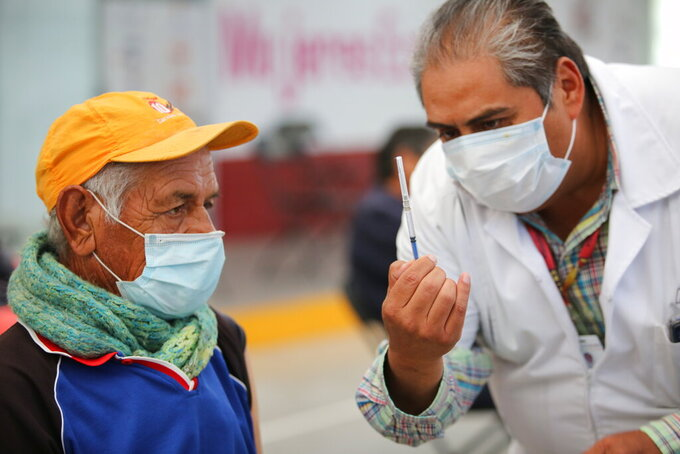 A nurse shows an elderly man a syringe prepared with dose of the Sinovac COVID-19 vaccine, before he is inoculated at the Americas Cultural Center, in Ecatepec, Mexico, Saturday, April 3, 2021. (AP Photo/Ginnette Riquelme)