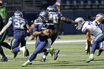 Seattle Seahawks quarterback Russell Wilson drops to make a touchdown pass to wide receiver Tyler Lockett during the first half of an NFL football game against the Dallas Cowboys, Sunday, Sept. 27, 2020, in Seattle. (AP Photo/John Froschauer)
