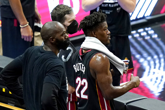 Miami Heat guard Goran Dragic, center, and forward Jimmy Butler (22) watch during the closing minutes of Game 4 of an NBA basketball first-round playoff series against the Milwaukee Bucks, Saturday, May 29, 2021, in Miami. The Bucks won 120-103. (AP Photo/Lynne Sladky)