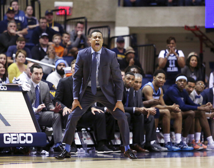 Rhode Island coach David Cox reacts from the sidelines against West Virginia during the second half of an NCAA college basketball game Sunday, Dec. 1, 2019, in Morgantown, W.Va. (AP Photo/Kathleen Batten)