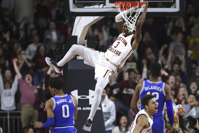 Boston College guard Jared Hamilton (3) lets out a scream as he hangs on the rim after a dunk against Duke during the first half of an NCAA college basketball game in Boston, Tuesday, Feb. 4, 2020. (AP Photo/Charles Krupa)