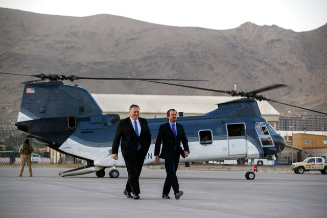 FILE - In this June 25, 2019 photo, Secretary of State Mike Pompeo, left, walks from a helicopter with U.S. Ambassador to Afghanistan John Bass. Bass is leaving Afghanistan, ending his two-year tenure as America's ambassador to the war-weary country that began in December 2017. (AP Photo/Jacquelyn Martin, Pool, File)