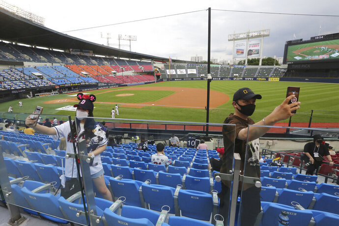 FILE - In this July 27, 2020, file photo, fans wearing face masks to help protect against the spread of the new coronavirus take a selfie before the KBO league game between Doosan Bears and LG Twins in Seoul. South Korea may have been way ahead of the international curve in getting sport back to some semblance of normality but instead of near-full stadiums watching the end of baseball and soccer seasons later this year, a recent spike in coronavirus cases means officials will settle for just finishing the season at all.(AP Photo/Ahn Young-joon, File)