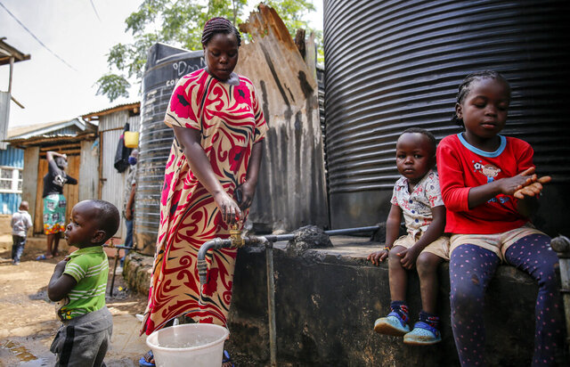 In this April 10, 2020, photo, Judith Andeka a widow and mother of five, fetches water with a bucket in the Kibera slum, or informal settlement, of Nairobi, Kenya. Andeka used to earn $2.50 to $4 a day washing clothes in Nairobi's Kibera, one of the world's biggest slums. With people not going to work because of restrictions on movement, neighbors can't afford her services. (AP Photo/Brian Inganga)
