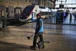 A station employee walks along an empty platform at the Gare St-Charles station, in Marseille, southern France, Sunday, Dec. 8, 2019, on the fourth day of nationwide strikes that disrupted weekend travel around France.  (AP Photo/Daniel Cole)