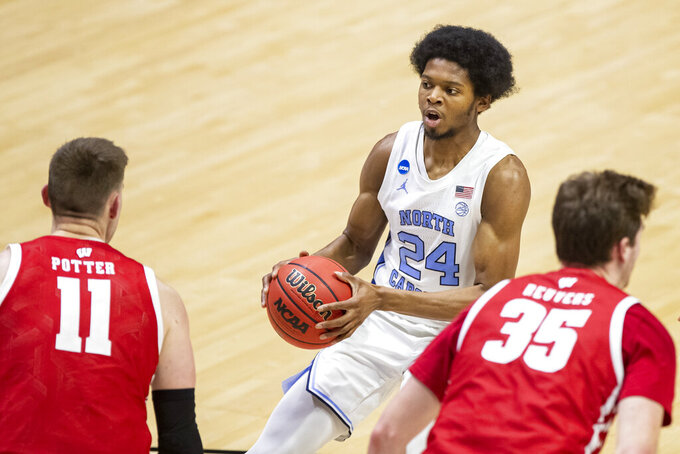 North Carolina's Kerwin Walton (24) drives against Wisconsin's Micah Potter (11) and Nate Reuvers (35) during the second half of a first-round game in the NCAA men's college basketball tournament, Friday, March 19, 2021, at Mackey Arena in West Lafayette, Ind. (AP Photo/Robert Franklin)
