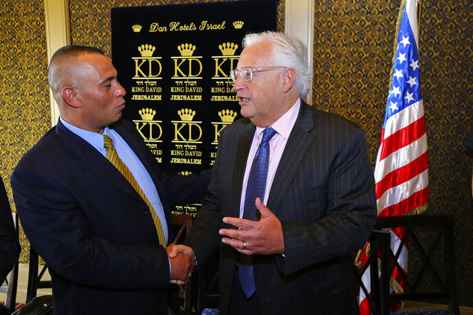 In this May 1, 2018 photo, Palestinian businessman Ashraf Jabari, left, shakes hands with U.S. Ambassador to Israel David Friedman at the King David Hotel in Jerusalem. Jabari, who flouts political taboos by working with Israeli settlers in the West Bank, could soon be playing a key role in President Donald Trump's Middle East peace plan, but he is reviled by fellow Palestinians who view him with suspicion. While Palestinian officials have rejected next month's planned conference in Bahrain, Jabari says he will be thrilled to attend. (AP Photo/Matanya Ofir)