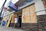 """FILE- In this Tuesday, Sept. 11, 2018, file photo a man walks out of the boarded up Robert's Grocery in Wrightsville Beach, N.C., in preparation for Hurricane Florence. Though it's far from clear how much economic havoc Hurricane Florence will inflict on the southeastern coast, from South Carolina through Virginia, the damage won't be easily or quickly overcome. In those states, critically important industries like tourism and agriculture are sure to suffer. """"These storms can be very disruptive to regional economies, and it takes time for them to recover,"""" said Ryan Sweet, an economist at Moody's Analytics. (Matt Born/The Star-News via AP, File)"""