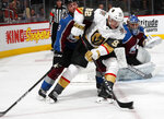 Vegas Golden Knights left wing Tomas Nosek, front, moves past Colorado Avalanche defenseman Samuel Girard to put a shot on goaltender Semyon Varlamov, back, in the second period of an NHL hockey game Monday, Feb. 18, 2019, in Denver. (AP Photo/David Zalubowski)