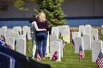 Two women embrace next to a grave at the veterans' cemetery at Mountview Cemetery in Billings, Mont., Monday, May 25, 2020. No new cases of the coronavirus were reported in Montana on Monday for the fifth straight day.  (AP Photo/Matthew Brown)