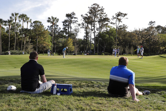 Fans watch players during the first round of The Players Championship golf tournament Thursday, March 12, 2020 in Ponte Vedra Beach, Fla. (AP Photo/Lynne Sladky)