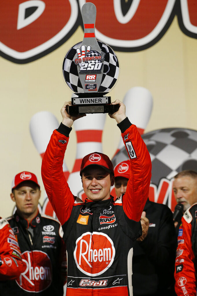 Christopher Bell holds the trophy as he celebrates his win in the NASCAR Xfinity Series auto race, in Victory Lane at Richmond Raceway in Richmond, Va., Friday, Sept. 20, 2019. (AP Photo/Steve Helber)