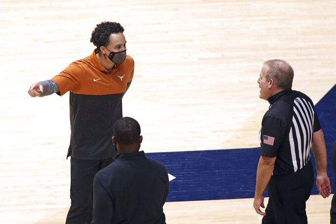 Texas coach Shaka Smart speaks with an official during the second half of an NCAA college basketball game against West Virginia, Saturday, Jan. 9, 2021, in Morgantown, W.Va. (AP Photo/Kathleen Batten)