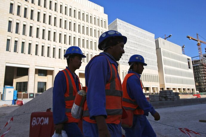 FILE- In this April 23, 2019 file photo, workers leave their construction sites at the Msheireb Downtown Doha district in Doha, Qatar. The energy-rich nation of Qatar is pledging to fully eliminate a labor system that ties workers to their employer and requires them to have their company's permission to leave the country. (AP Photo/Kamran Jebreili, File)