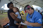 A woman holds a baby to be attended at a tent-hospital setup by Samaritans Purse in the aftermath of Hurricane Dorian in Freeport, Bahamas, Tuesday, Sept. 10, 2019. Thousands of hurricane survivors are facing the prospect of starting their lives over but with little idea of how or where to even begin. (AP Photo/Ramon Espinosa)