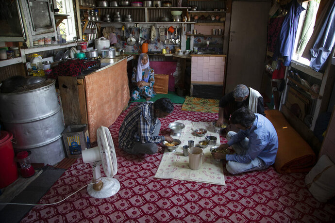 """Kashmiri man Ghulam Qadir Ota and family members eat a meal inside their house boat during lockdown to stop the spread of the coronavirus at a Nigeen Lake in Srinagar, Indian controlled Kashmir, July 24, 2020. """"We've not earned a single penny for a year now, all we have are these boats, We don't have any other means to earn,"""