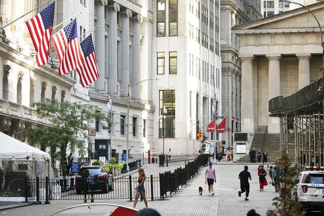 FILE - People walk by the New York Stock Exchange, left, Tuesday, July 21, 2020.  Wall Street is drifting in early trading on Monday, Aug. 10,  after President Donald Trump announced several stopgap moves to aid the economy.   (AP Photo/Mark Lennihan)