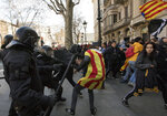 Catalan police officers clash with demonstrators outside a subway after blocking a train rail, during a general strike in Catalonia, Spain, Thursday, Feb. 21, 2019. Protesters backing Catalonia's secession from Spain clashed with police and blocked major roads and train tracks across the northeastern region on Thursday during a strike called to protest the trial of a dozen separatist leaders. (AP Photo/Emilio Morenatti)