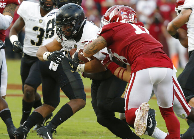 FILE - In this Sept. 22, 2018, file photo, Army' Darnell Woolfolk (33) carries as Oklahoma linebacker Curtis Bolton (18) defends during an NCAA college football game in Norman, Okla. Army quarterback Kelvin Hopkins Jr. and fullback Woolfolk are leading the team with 671 and 665 yards rushing, respectively. Woolfolk tops the team with nine TDs, one more than his backfield mate, heading into this week's game against Lafayette. (AP Photo/Sue Ogrocki, File)